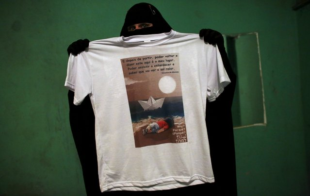 Gisele Marie, a Muslim woman and professional heavy metal musician, holds a T-shirt with a drawing depicting the drowned Syrian toddler Aylan Kurdi during a fund raising concert for the Syrian refugees in Brazil, in Rio de Janeiro, November 8, 2015. (Photo by Nacho Doce/Reuters)