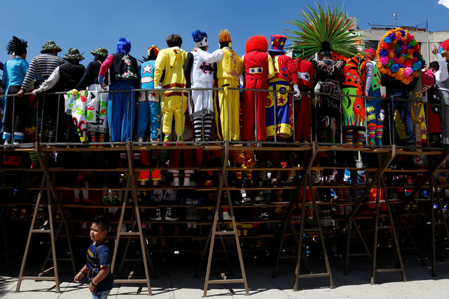 A child is seen behind the clowns as the posse for the annual picture as part of the XXI Convention of Clowns, at the Monument to the Revolution, in Mexico City, Mexico, October 19, 2016. (Photo by Carlos Jasso/Reuters)
