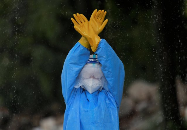 A female soldier wearing personal protective equipment (PPE) disinfects herself during a training on how to handle bodies of coronavirus victims, amidst the spread of the coronavirus disease (COVID-19), in Kathmandu, Nepal on October 15, 2020. (Photo by Navesh Chitrakar/Reuters)