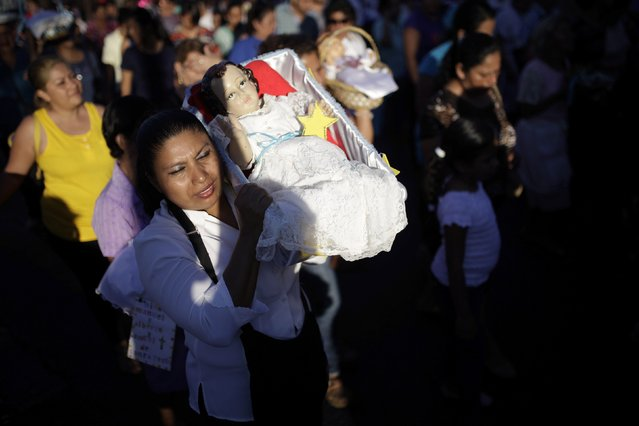 A Catholic woman holds a figurine of baby Jesus during a religious procession on Holy Innocents Day in Antiguo Cuscatlan, on the outskirts of San Salvador, December 28, 2014. (Photo by Jose Cabezas/Reuters)