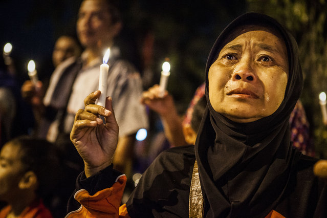 A woman cries as she prays for the victims of the AirAsia flight QZ8501 crash at the Indonesian Air Force Military Base Operation Airport on December 31, 2014 in Surabaya, Indonesia. (Photo by Oscar Siagian/Getty Images)