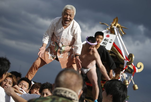"Men ride on a ""mikoshi"" or portable shrine as local people carry it into the sea during a festival to wish for calm waters in the ocean and good fortune in the new year in Oiso, west of Tokyo, January 1, 2015. (Photo by Yuya Shino/Reuters)"