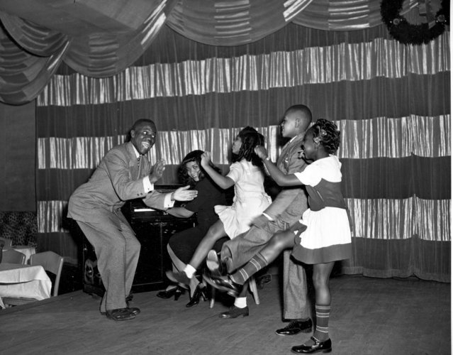 "Tap dancer Bill Robinson, known as Bojangles, far left, is assisted by Mary Bruce on piano as he leads young dancers to the ""Charleston Walk"" in New York City on December 27, 1944.  The children, from left, are, Dorothy Williams, 6; John Whitefield, 8; and Dolgres Jackson, 5. (Photo by AP Photo)"
