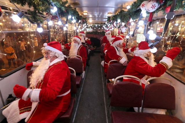 "Musicians in Father Frost costumes ride along Nevsky Avenue on the Dedmorobus (portmanteau of ""Father Frost"" and ""bus"") musical bus to entertain citizens ahead of New Year celebrations in St Petersburg, Russia on December 28, 2020. (Photo by Alexander Demianchuk/TASS)"