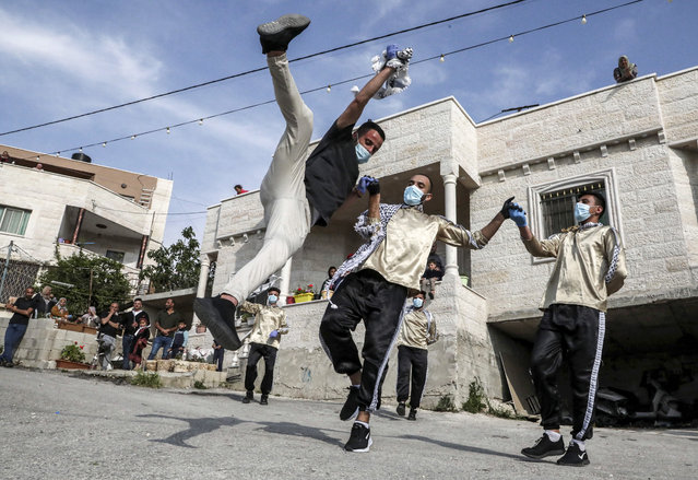 Dancers of the Palestinian Jafra Dabke Team perform a traditional dabke dance while wearing latex gloves and surgical masks for people confined due to a COVID-19 coronavirus pandemic lockdown in the village of Tarqumia northwest of Hebron in the occupied West Bank, on April 15, 2020. (Photo by Hazem Bader/AFP Photo)