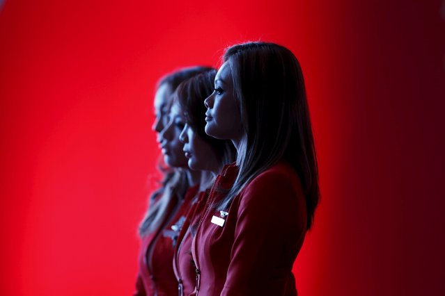 Flight attendants of the long-haul carrier AirAsia X watch a performance during the launch of the company's prospectus in Kuala Lumpur in this June 10, 2013 file photo. AirAsia X is expected to report Q3 results this week. (Photo by Bazuki Muhammad/Reuters)