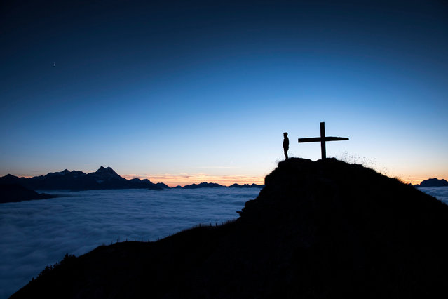 An image made available 06 October shows a person watching the sunset above the sea of fog on the summit of the Croix des Chaux/Chaux Ronde (2012m) above Gryon VD, western Switzerland, 05 October 2016. (Photo by Anthony Anex/EPA)