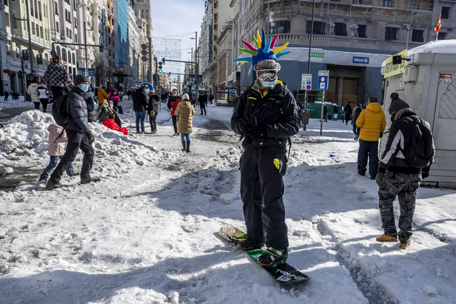 A man snowboards at the Gran Via avenue in downtown Madrid, Spain, Sunday, January 10, 2021. A large part of central Spain including the capital of Madrid are slowly clearing snow after the country's worst snowstorm in recent memory. (Photo by Manu Fernandez/AP Photo)