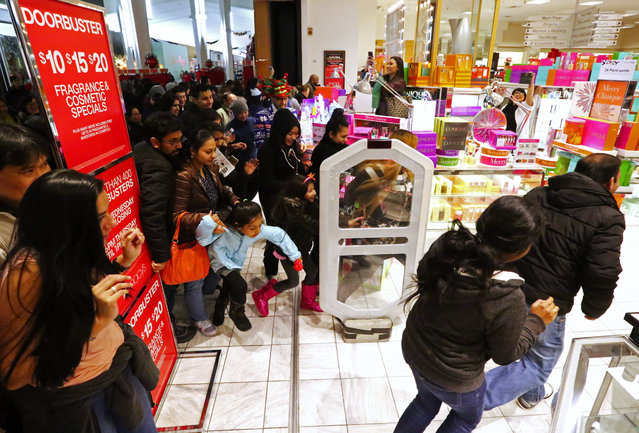 A crowd at Macy's rushes into the store at 6 p.m. on Thanksgiving Day at Westfield Southcenter mall Thurs., November 26, 2015, in Tukwila. (Photo by Ken Lambert/The Seattle Times)