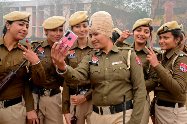 Police personnel take a selfie after taking part in a rehearsal for the upcoming Republic Day Parade in Amritsar on January 15, 2021. (Photo by Narinder Nanu/AFP Photo)