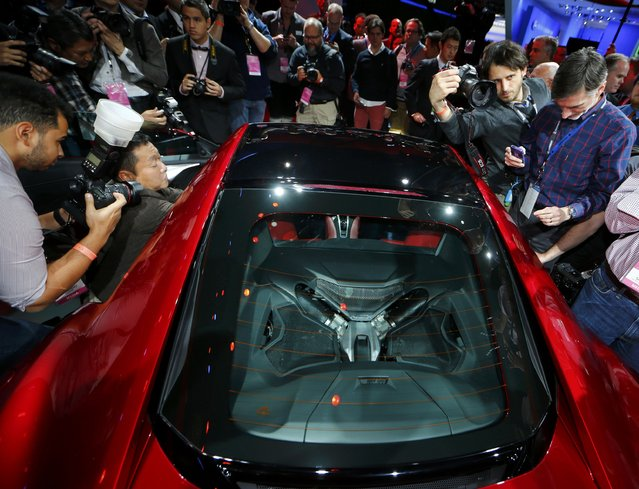 Members of the media crowd around the 2015 Acura NSX as it is displayed during the first press preview day of the North American International Auto Show in Detroit, Michigan, January 12, 2015. (Photo by Mark Blinch/Reuters)