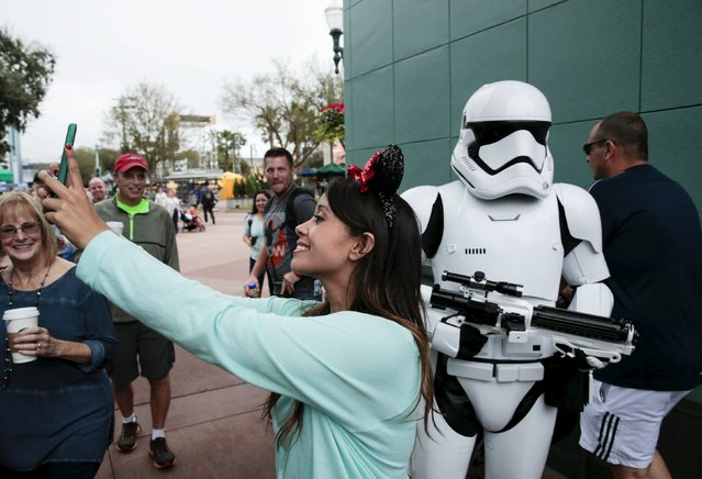 A Disney guest takes a selfie with a person dressed as a stormtrooper outside Star Wars Launch Bay during its grand opening at Disney's Hollywood Studios in Orlando, Florida December 4, 2015. (Photo by Scott Audette/Reuters)