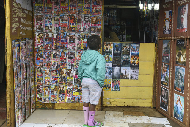 A boy looks at the cover pictures of some recent DVDs' at a movie shop in Kibera, the largest slum in the city of Nairobi, Kenya on June 19, 2018. (Photo by Simon Maina/AFP Photo)