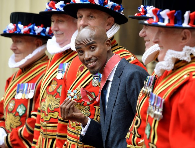 Double Olympic gold medal winning athlete Mo Farah holds his CBE medal, after he received the award from the Prince of Wales during an Investiture ceremony at Buckingham Palace in central London, on  June 28, 2013. (Photo by John Stillwell/PA Wire)