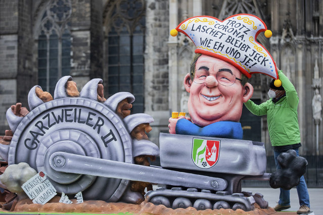 """A carnival float designed by the environment organization Greenpeace and depicting North Rhine-Westphalia state governor Armin Laschet in a lignite mining dredger, stands in front of Cologne Cathedral in protest against his climate policy in Cologne, Germany, Monday, February 15, 2021. The slogan on the hat reads: """"Despite Corona, Laschet is as mad as ever"""". (Photo by Rolf Vennenbernd/dpa via AP Photo)"""