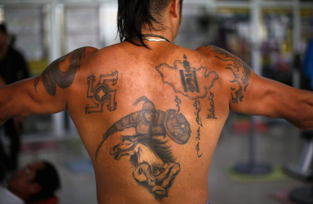 Tattoos are seen on the back of a member of a self-described skinhead group as he trains at a gym in Ulan Bator June 22, 2013.  (Photo by Carlos Barria/Reuters)
