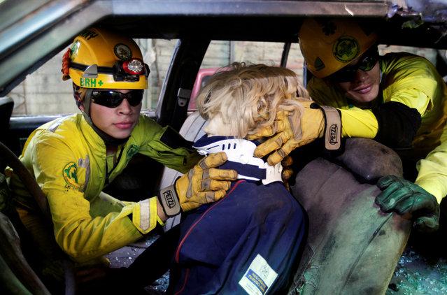Comandos de Salvamento rescuers Brandon Martinez (L) and Brayan Hernandez participate in a car accident rescue practice in San Salvador, El Salvador July 27, 2016. (Photo by Jose Cabezas/Reuters)