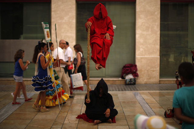 Women wearing traditional Sevillana dresses (L) walk past street performers at Marques de Larios street in downtown Malaga, southern Spain, July 18, 2013. (Photo by Jon Nazca/Reuters)