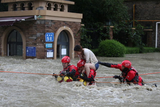 Firefighters rescue a stranded woman on a flooded street, following heavy rainfall in Chengdu, Sichuan province, China on July 12, 2018. (Photo by Wang Hongqiang/Chengdu Economic Daily via Reuters)