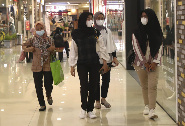 Women wearing face masks as a precaution against coronavirus outbreak walk at a shopping mall in Tangerang, Indonesia, Monday, March 1, 2021. (Photo by Tatan Syuflana/AP Photo)