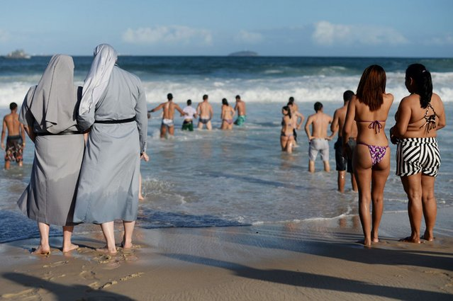 Two Polish nuns look at people bathing as hundreds of thousands of young Catholic pilgrims attend the World Youth Day gathering at Copacabana beach in Rio de Janeiro. (Photo by Yasuyoshi Chiba/AFP Photo)