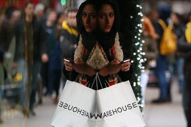 A woman waits with her shopping bags on December 24, 2014 in London, England. Up to 800m GBP is expected to be spent in a last minute, Christmas Eve, dash for presents. (Photo by Carl Court/Getty Images)