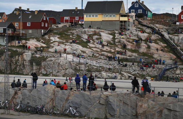 People watch as local soccer teams play on July 18, 2013 in Ilulissat, Greenland. As Greenlanders adapt to the changing climate and go on with their lives, researchers from the National Science Foundation and other organizations are studying the phenomena of the melting glaciers and its long-term ramifications for the rest of the world. (Photo by Joe Raedle/Getty Images via The Atlantic)