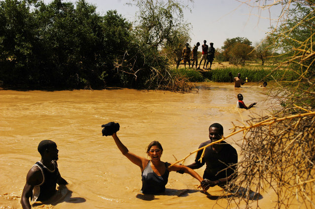 Photographer Lynsey Addario keeps her camera dry while crossing a river in southern Sudan in 2004. (Photo by Lynsey Addario)