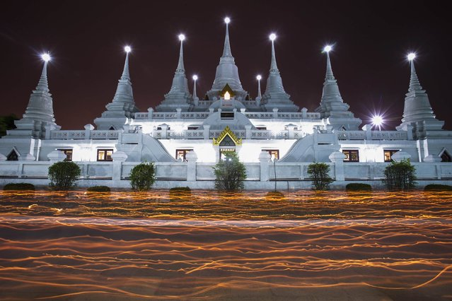 Buddhists hold candles as they encircle the Wat Asokaram Temple during Asanha Puja Day, the eve of the Buddhist Lent, in Samut Prakan July 11, 2014. (Photo by Athit Perawongmetha/Reuters)
