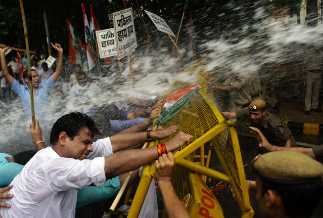 Activists of India's Congress party's youth wing try to break barricades as police use water cannon to stop them during a protest against the death of five Indian army soldiers in cross-border exchanges, New Delhi, India, Wednesday, Aug 7, 2013. India's army says five of its soldiers were killed and another wounded when Pakistani troops fired at a patrol near the cease-fire line in the disputed Himalayan region of Kashmir on Tuesday. The incident could threaten recent overtures aimed at resuming peace talks between the nuclear-armed rivals. (Photo by Tsering Topgyal/AP Photo)