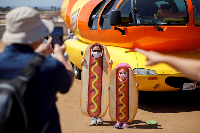 "A family takes a picture at the Oscar Myer Wienermobile during a visit to ""The Flower Fields"", as California opens up from the pandemic, in Carlsbad, California, U.S., March 31, 2021. (Photo by Mike Blake/Reuters)"