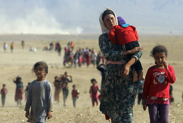 Displaced people from the minority Yazidi sect, fleeing violence from forces loyal to the Islamic State in Sinjar town, walk towards the Syrian border on the outskirts of Sinjar mountain near the Syrian border town of Elierbeh of Al-Hasakah Governorate in this August 11, 2014 file photo. (Photo by Rodi Said/Reuters)