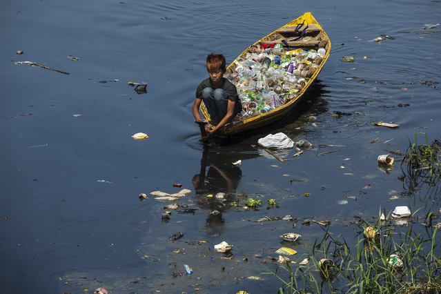 A boy collecting plastic waste to sell navigates water made black by industrial pollution on the Citarum river on August 28, 2018 outside Bandung, Java, Indonesia. (Photo by Ed Wray/Getty Images)