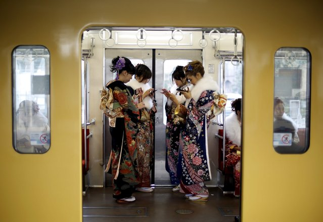 Japanese women wearing kimonos look at their mobile phones after their Coming of Age Day celebration ceremony at an amusement park in Tokyo January 11, 2016. (Photo by Yuya Shino/Reuters)
