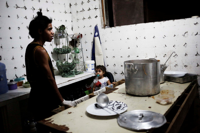 A baby looks at Gaby, 18, who is among members of lesbian, gay, bisexual and transgender (LGBT) community, that have been invited to live in a building that the roofless movement has occupied, inside a kitchen, in downtown Sao Paulo, Brazil, November 10, 2016. (Photo by Nacho Doce/Reuters)