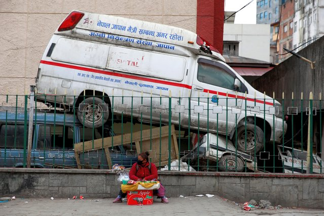 A street vendor sits next to an abandoned ambulance outside the premises of a hospital as the major second coronavirus wave surges in Kathmandu, Nepal on May 4, 2021. (Photo by Navesh Chitrakar/Reuters)