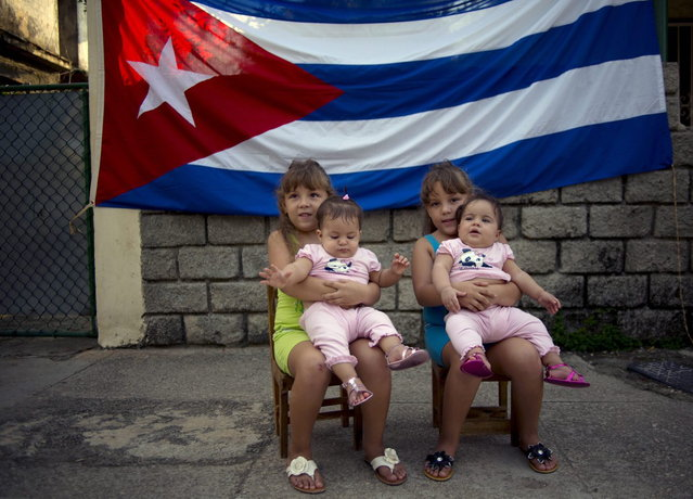 In this September 29, 2013 photo, six-year-old twins Asley and Aslen Velazquez hold eight-month-old twins Tiffani and Stessany Valles as they pose for portraits in front a Cuban flag on their street in Havana, Cuba. While there's been no scholarly study of the 12 sets of twins on 68-A Street, they nonetheless consider themselves part of a special community. (Photo by Ramon Espinosa/AP Photo)