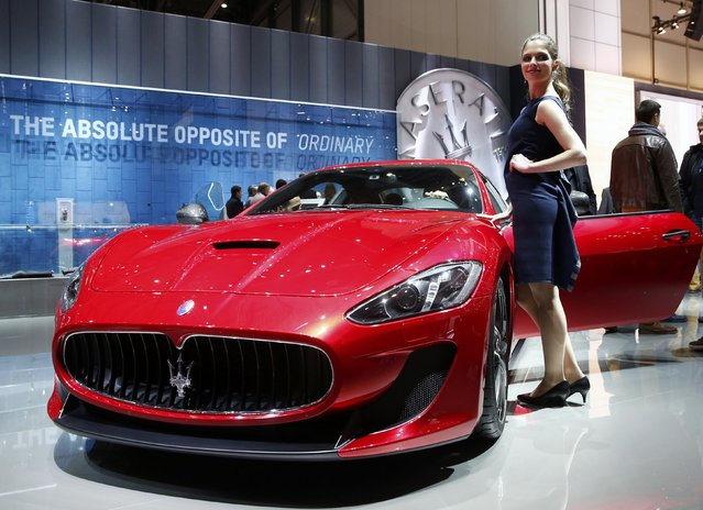 A model poses next to a  Maserati GranTurismo MC Stradale during the second press day ahead of the 85th International Motor Show in Geneva March 4, 2015. REUTERS/Arnd Wiegmann
