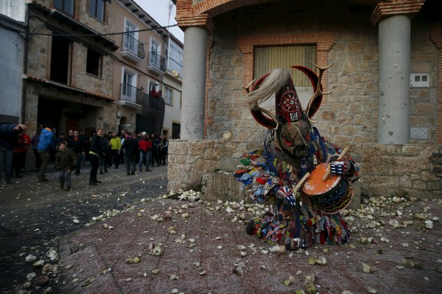 Revellers throw turnips at the Jarramplas, a character who wears a devil-like mask and a colourful costume, as he makes his way through the streets while beating his drum during the Jarramplas traditional festival in Piornal, southwestern Spain, January 19, 2016. (Photo by Susana Vera/Reuters)