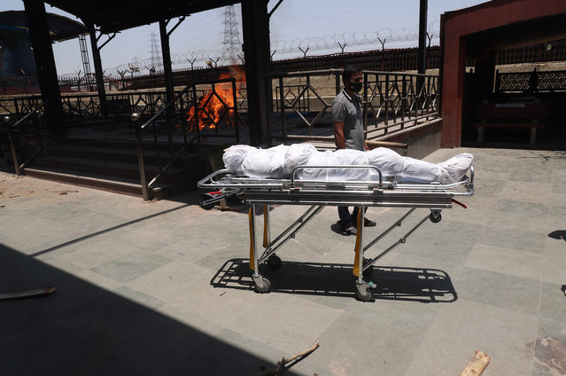 The body of a person who died of COVID-19 waits to be cremated at a crematorium New Delhi, India, Thursday, May 27, 2021. (Photo by Amit Sharma/AP Photo)