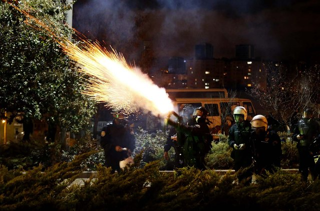 Police fire tear gas to disperse university students demonstrating against reconstruction plans that includes a part of their campus in Ankara, Turkey, on Oktober 19, 2013. The municipality plan opposed by the students involves building a road across the Middle East Technical University campus and uprooting a large number of trees in the area. (Photo by Umit Bektas/Reuters)