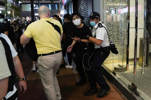 A police officer detains a man at Causeway Bay on the 32nd anniversary of the crackdown on pro-democracy demonstrators at Beijing's Tiananmen Square in 1989, in Hong Kong, China on June 4, 2021. (Photo by Lam Yik/Reuters)