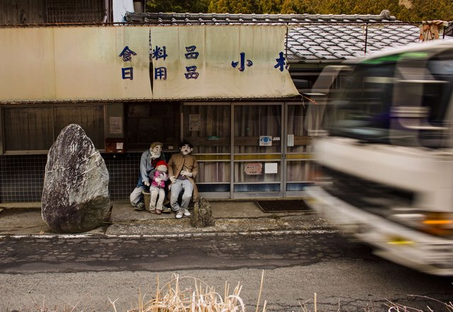 A vehicle drives past scarecrows sitting outside a closed down shop in the village of Nagoro on Shikoku Island in southern Japan February 24, 2015. Tsukimi Ayano made her first scarecrow 13 years ago to frighten off birds pecking at seeds in her garden. The life-sized straw doll resembled her father, so she made more. (Photo by Thomas Peter/Reuters)