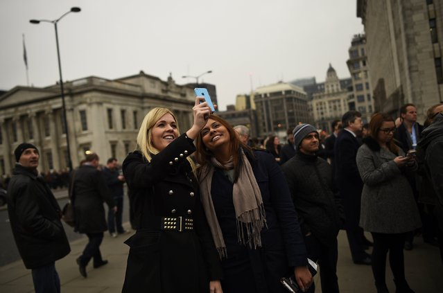 Commuters stop to stare and take photographs as they try to see a partial solar eclipse from London Bridge in London March 20, 2015. (Photo by Dylan Martinez/Reuters)