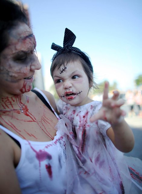 A child dressed as a zombie poses before a 'Zombie Walk' along Copacabana Beach during Day of the Dead festivities on November 2, 2013 in Rio de Janeiro, Brazil. Brazilians often mark the traditional Latin American holiday by visiting loved ones' graves while the Zombie Walk offers a modern twist. (Photo by Mario Tama/Getty Images)