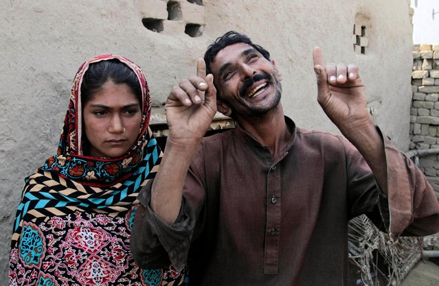 "In this Tuesday, December 20, 2016 photo, Mohammad Ramzan, right, reacts while talking to The Associated Press with his young bride Saima in Jampur, Pakistan. Saima was given as a bride to the older man by her father so he could marry the groom's sister, a practice of exchanging girls that is entrenched in conservative regions of Pakistan. It even has its own name in Urdu: Watta Satta, ""give and take"". A mix of interests – family obligations, desire for sons, a wish to hand off a girl to a husband – can lead to a young teen in an a marriage she never sought. (Photo by K.M. Chaudhry/AP Photo)"