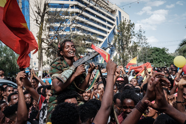 """Female soldiers of Tigray Defence Force (TDF) celebrate while they sit on men's shoulders as people celebrate their return on a street in Mekele, the capital of Tigray region, Ethiopia, on June 29, 2021. Rebel fighters in Ethiopia's war-hit Tigray seized control of more territory on June 29, 2021, one day after retaking the local capital and vowing to drive all """"enemies"""" out of the region. (Photo by Yasuyoshi Chiba/AFP Photo)"""