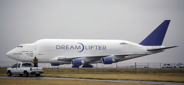A man takes a photo of the Boeing 747 LCF Dreamlifter from the back of his truck, Thursday, November 21, 2013, after the aircraft accidentally landed at Col. James Jabara Airport in Wichita, Kan. Wednesday night. Boeing says the Dreamlifter, a 747 jumbo jet used to haul parts for construction of its new 787 Dreamliner, landed safely at Jabara, about eight miles from McConnell Air Force Base in Wichita where it was supposed to land. (Photo by Jaime Green/AP Photo/Wichita Eagle)