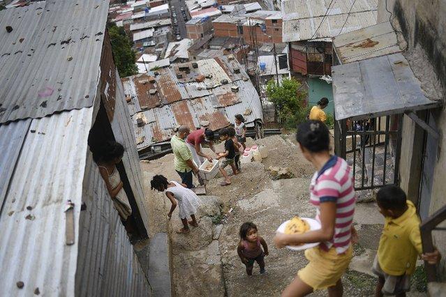 Residents pass out cornmeal cakes known locally as arepas, in the Altos de Lidice community of Caracas, Venezuela, Saturday, June 5, 2021, amid the coronavirus pandemic. (Photo by Matias Delacroix/AP Photo)