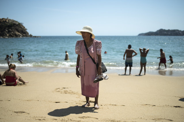 A woman makes her way out of the water on April 1, 2015 in Acapulco, Mexico. (Photo by Jonathan Levinson/The Washington Post)